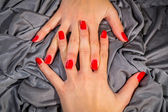 Beautiful female hands with red nail polish on the nails — Stock Photo