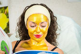 Woman in gold facial mask reading magazine — Stockfoto