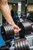 Homme faire les exercices avec haltères dans la salle de gym. — Photo