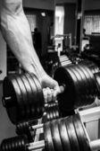 Hombre haciendo ejercicios con pesas en el gimnasio — Foto de Stock