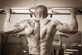 Man with a tattoo  exercising in gym — Stock Photo