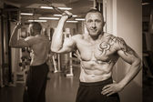 Man with a tattoo  exercising in gym — 图库照片