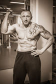 Man with a tattoo  exercising in gym — Foto de Stock