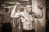 Man with a tattoo  exercising in gym — Stockfoto