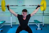 Sportsman pushing barbell — Foto de Stock