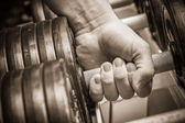 Mans hand with dumbbells. — Stock Photo