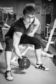 Man in a gym with dumbbells — Stock Photo