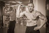 Man with tattoo in the gym — Stock Photo