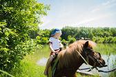 Boy riding pony — Stock Photo