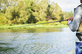 Fisherman holding spinning — Stock Photo
