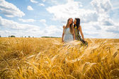 Girls standing in a wheat field. — Stock Photo