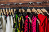 Many blouses on hangers in the dressing room. — Stock Photo
