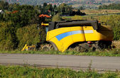 Yellow combine harvester — Stock Photo