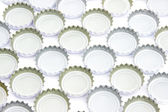 Background of used beer caps over white — Stock Photo