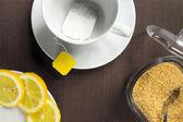 Tea cup, slices of lemon and brown sugar — Stock Photo