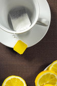 Tea cup and slices of lemon — Stock Photo