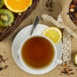 Stock Photo: Hot cup of tea, herbal leaves and ripe fruits