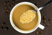 Brown sugar on a spoon and a cup of coffee — Stock Photo