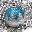 Silver and blue bauble on string of silver beads — Stock Photo