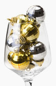 Gold and silver baubles in a wine glass — Stock Photo