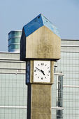 Clock tower in front of office buildings — Stock Photo