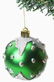 Green bauble hanging on a Christmas tree — Stock Photo