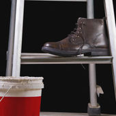 Leather boot on a step ladder — Stock Photo