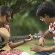 Woman playing guitar with her boyfriend — Stock Photo