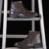 Leather boots on a step ladder — Stock Photo