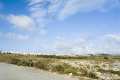 Road with a township in the background — Stock Photo