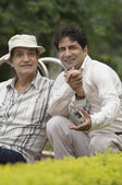 Man with his father in a park — Stock Photo