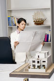 Businesswoman looking at a blueprint in an office — Stock Photo