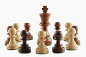 King surrounded by chess pawns — Stock Photo