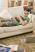 Man lying on a couch and listening to music — Stock Photo