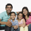 Happy family sitting on a couch — Stockfoto