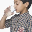 Schoolboy drinking glass of water — Stock Photo #32968281