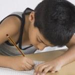 Boy doing homework at desk — Stock Photo #32968355