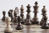 White pawn facing black chess pieces — Stok fotoğraf