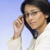 предприниматель, держа ее очки — Стоковое фото