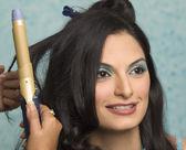 Mão encaracolar o cabelo de uma mulher jovem — Fotografia Stock