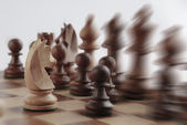 White knight facing black chess pieces — Stockfoto