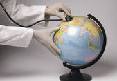 Hands examining a globe with a stethoscope — Stock Photo