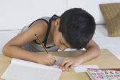 Boy doing homework at desk — Stock Photo