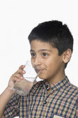 Schoolboy drinking a glass of water — Stock Photo