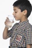Schoolboy drinking a glass of water — Stock fotografie