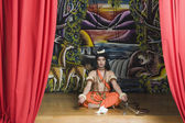 Stage artist dressed-up as Rama and praying — Stock Photo