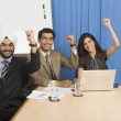 Business executives raising hands in an office — Stock Photo