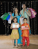 Family carrying shopping bags and gifts for Diwali — Stock Photo