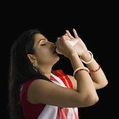 Kadın kabuklu deniz hayvanı kabuğu üfleme bengalli bir sari — Stok fotoğraf
