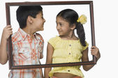 Girl and a boy holding an empty picture frame — Stock Photo